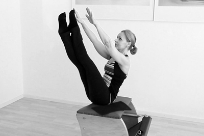Catarina Palma on the Wooden chair in the Pilates Studio Palma Personal Training Den Haag